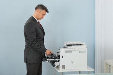 Businessman Fixing Cartridge In Printer Machine At Office