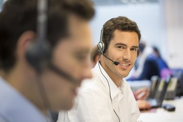 Businessman at office on the phone with headset, looking camera