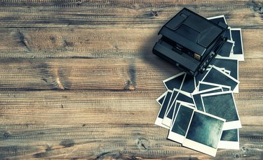 Polaroid photo frames and camera on rustic wooden background. retro style toned picture
