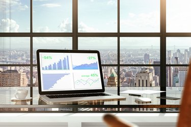Financial statistics on laptop screen on glassy table in modern
