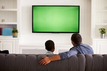 Father and son watching TV at home together, back view