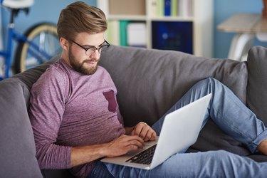 Stylish man using laptop at home