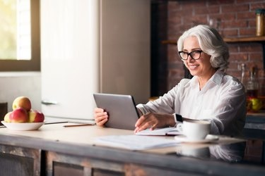 Elegant elderly woman using laptop
