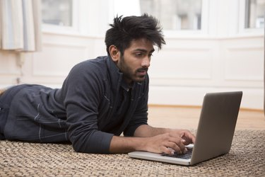 Indian Man lying on floor at home and using laptop.