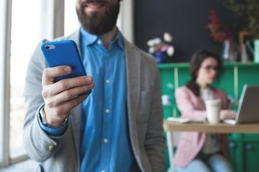 A bearded business man in glass looking at his phone