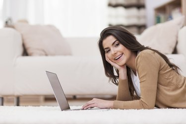 Smiling woman relaxing at home with laptop