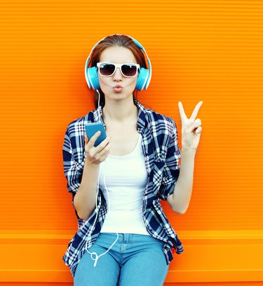 Pretty cool girl having fun and listens music in headphones
