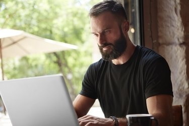 Concentrated Bearded Man Wearing Black Tshirt Working Laptop Wood Table