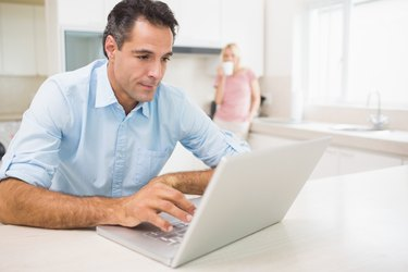 Man using laptop with woman drinking coffee at kitchen