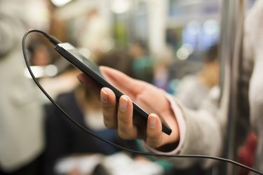 Woman listens to music with her cell phone in subway