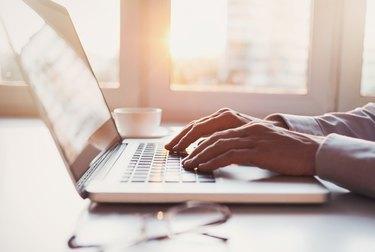 Place of work, man using laptop computer