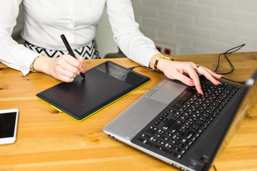 Close-up of designer using graphics tablet while working with