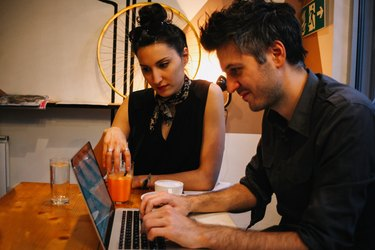 Young couple sitting in a coffee shop using laptop