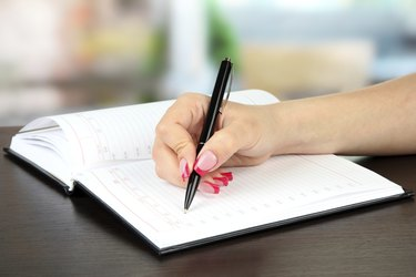 Hand signing in notebook, on bright background