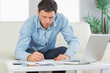 Serious casual man writing on sheets paying bills
