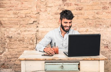 Young hipster guy sitting at vintage desk with laptop