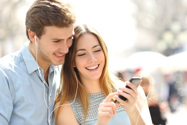 Couple sharing music from a smart phone on the street
