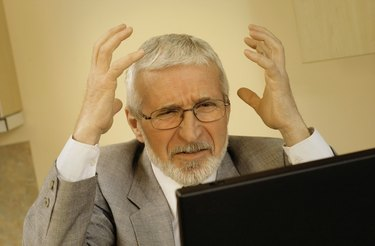 Mature businessman with hands raised in frustration and laptop computer, close-up