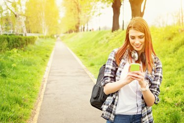Happy redhead high school girl with smart phone texting
