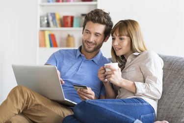 Mid adult couple shopping using laptop and credit card