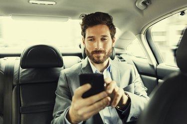 Hipster man in car Typing text message  on mobile phone
