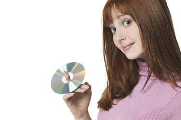 close up shot of a teenage female as she holds up a cd on her finger