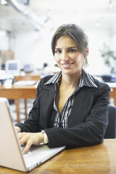 Portrait of a businesswoman using a laptop and smiling