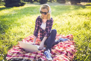 Girl on the grass using laptop