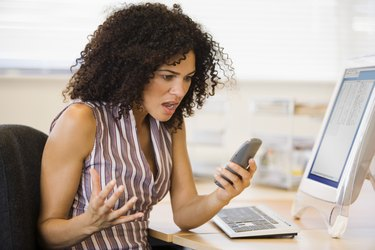 Angry businesswoman holding phone at desk