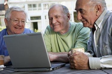 Three senior men looking at laptop computer screen, smiling, close-up