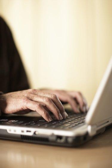 Senior man using laptop, close-up of hands