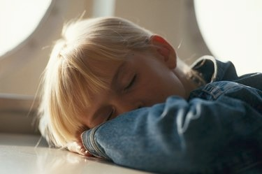Girl (4-7) resting on table, close-up