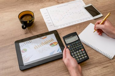 business concept - graph, calculator, tablet and pen on desk
