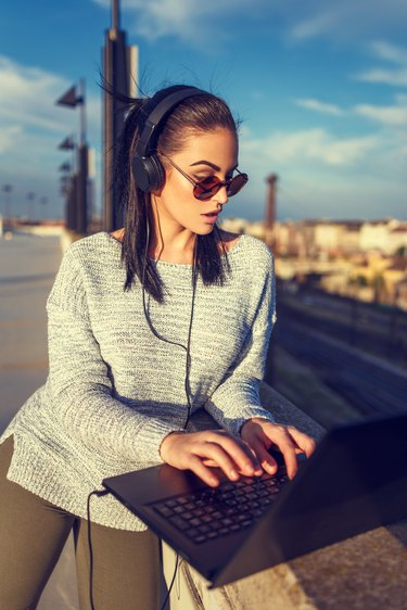 Young hipster woman typing on laptop outdoor