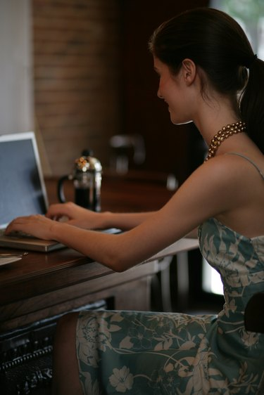 Young woman using laptop at bar in cafe.