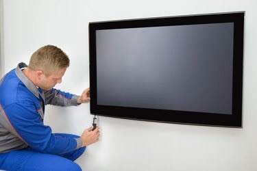 A repairman fixing a television