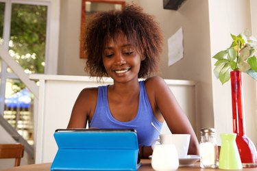 Smiling young woman using digital tablet at cafe