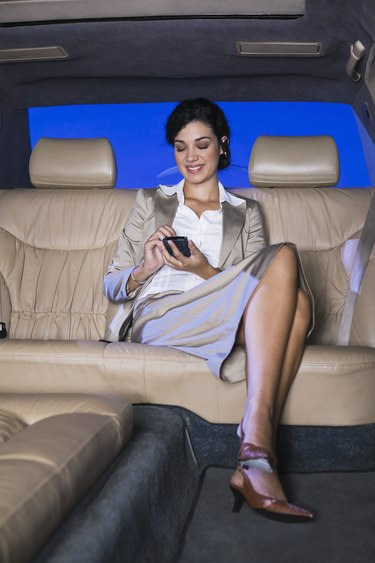 Businesswoman with cell phone in limousine
