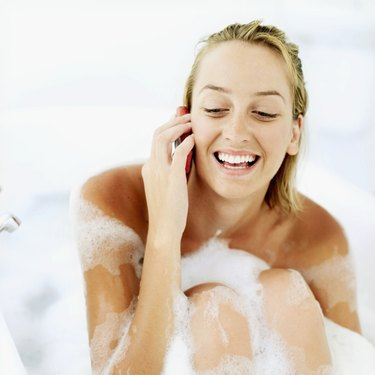 Close-up of a young woman smiling and talking on mobile phone in a bathtub