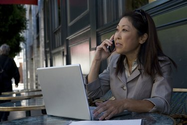 Businesswoman using laptop and mobile phone