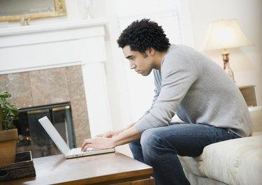 African man typing on laptop