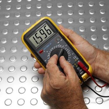 Hands using voltage meter