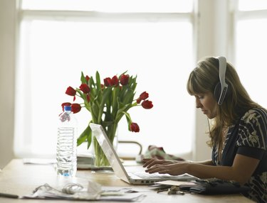 Young woman wearing headphones using laptop on dining table