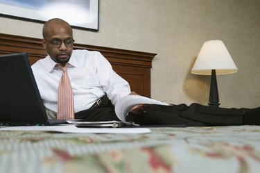 Businessman lying on a bed with a laptop beside him