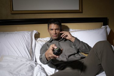 Man lying on bed, watching television