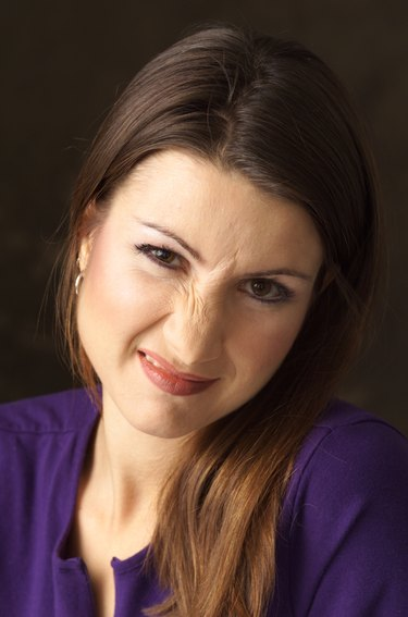 a caucasian young woman in a purple shirt with long brown hair in cocking her head to the side and scrunching her nose in disgust