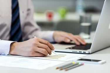 Business Person reading Data on paper Charts and Computer