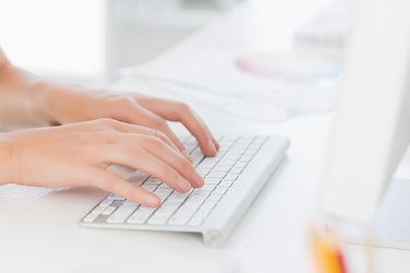 Close-up of hands using computer keyboard in office