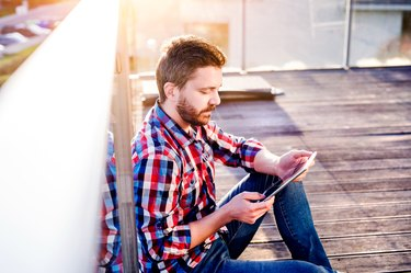 Businessman working from home on tablet, sitting on balcony