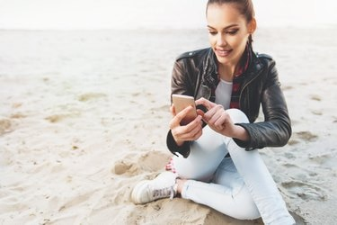Cute, young woman using a cell phone on the sand
